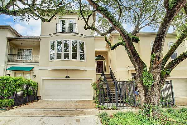Photo #1 Beautiful oak trees frame this three story townhome in a fantastic neighborhood! Second floor entrance.