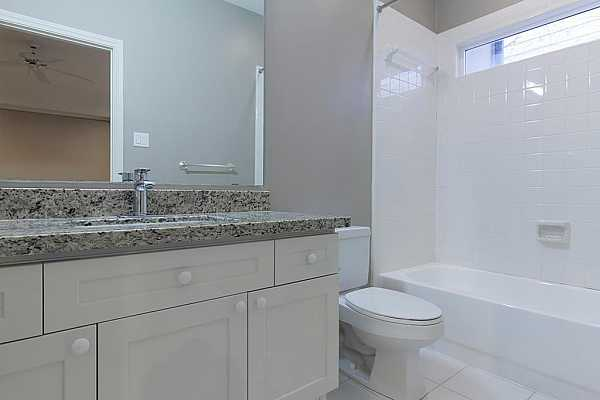 Photo #11 Full bathroom on first floor with granite countertops and updated sinks, faucets and fixtures.