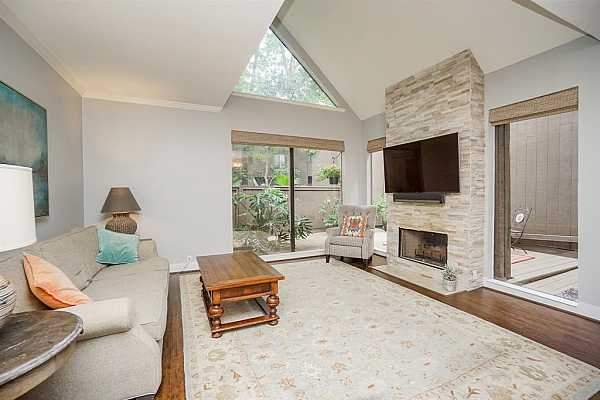 Photo #3 Large living room with updated fireplace, tons of natural light, pull-down shade window coverings, vaulted ceilings, crown molding throughout and floors.