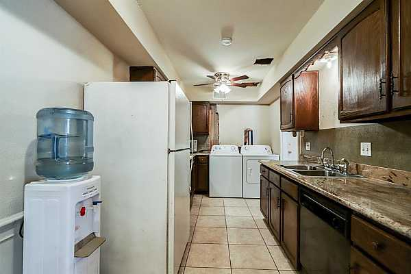 Photo #11 This view of the kitchen shows the laundry area. All appliances remain.