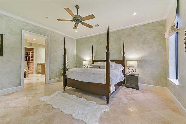 Photo #12 Spacious primary bedroom with custom wallpaper and travertine floors.
