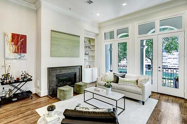 Photo #5 This living room features 12 foot high ceilings, elegant crown molding, wood floors and a gas log fireplace.