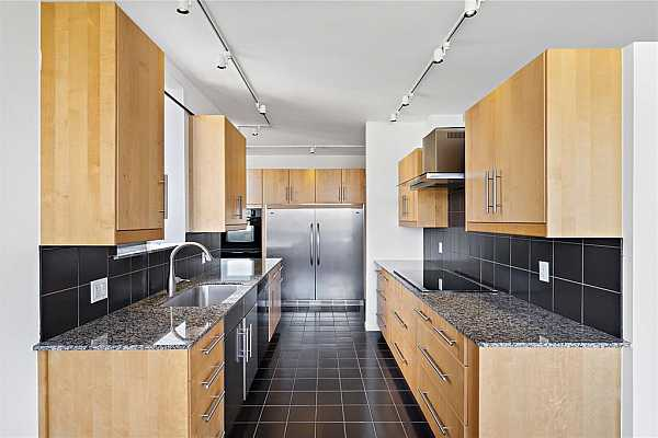 Photo #4 This sleek, modern entertaining kitchen is where you prepare that special meal. Black tiled walls, flat-front cabinetry, and granite countertops deck this beautiful kitchen.