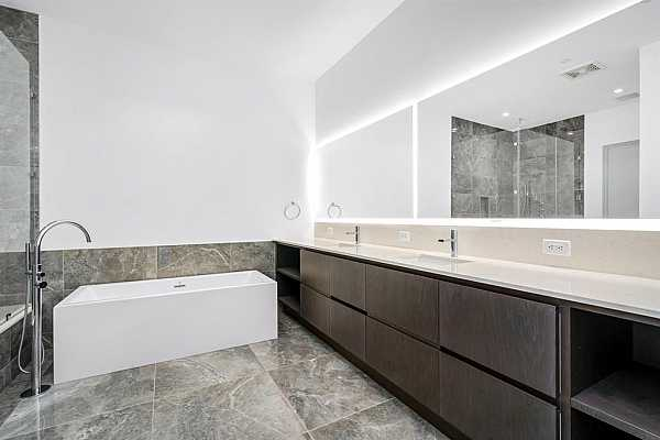 Photo #12 The primary bathroom is draped in flawless quartz and illuminated by in-lit mirrors.