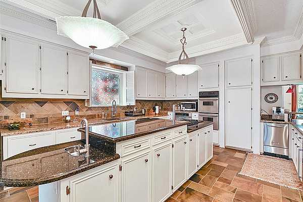 Photo #9 Gourmet Kitchen includes a crown molding with stainless steel chandeliers over the elongated center island with areas of different levels for taller Chef