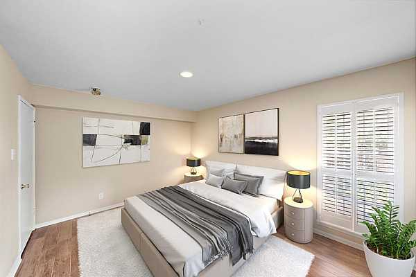 Photo #4 The primary bedroom features windows that bring in plenty of natural light with plantation shutters and easy maintenance wood-grain tile floors. This photo has been virtually staged to show furniture possibilities.