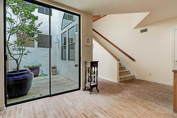 Photo #5 Gathering Space with brick tile flooring is just inside the double front doors.  The large glass window/door opens to delightful inner courtyard/patio that bring extra sunlight into the home.