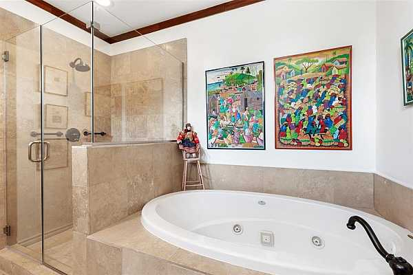Photo #12 The primary bath features a jetted tub and spacious shower.