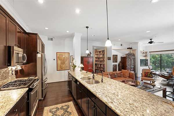 Photo #8 The kitchen features a massive center island with granite counter tops.