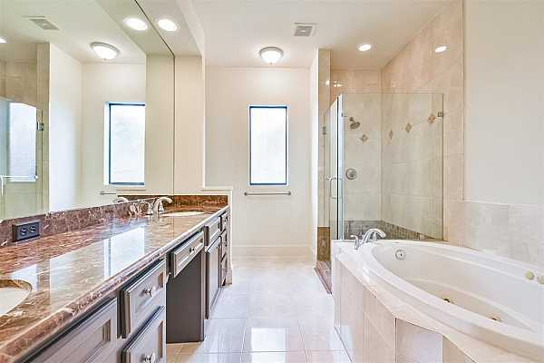 Photo #10 Luxurious primary bathroom with double sinks + vanity space, separate soaking tub and glass shower.