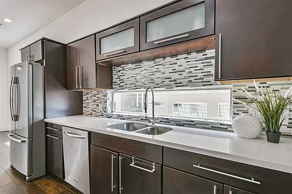 Photo #11 The cook of the family is certain to appreciate the stainless appliances that include a 5 burner gas cooktop, included French door refrigerator, oven, dishwasher, and built-in microwave, as well as the dual basin sink with a gooseneck pull-down faucet.