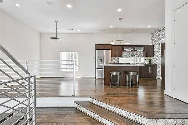 Photo #9 A few steps up from the family room, this sunlit dining space features handsome hardwood floors with a metal railing overlooking the staircase, recessed lighting, a pendant light over the table, and effortless access to the kitchen.