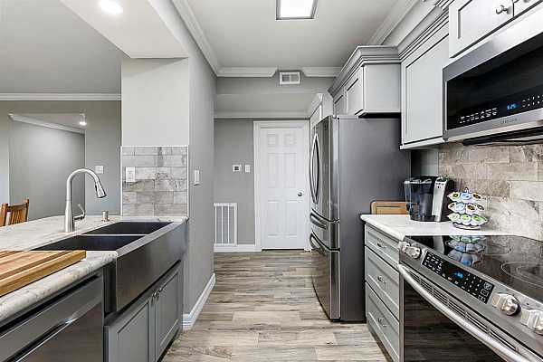Photo #3 Completely renovated kitchen with designer finishes, custom cabinetry, and upgraded appliances.
