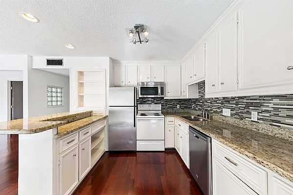 Photo #6 Kitchen features granite countertops and plenty of cabinet storage.