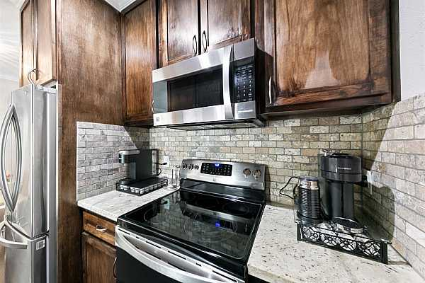 Photo #7 Upgraded cabinets flush with the ceiling, stainless steel appliances