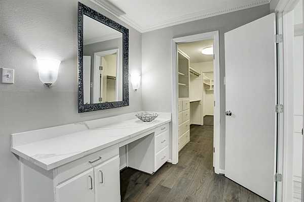 Photo #11 Primary updated  large bedroom with crown molding and vanity areaVirtually staged