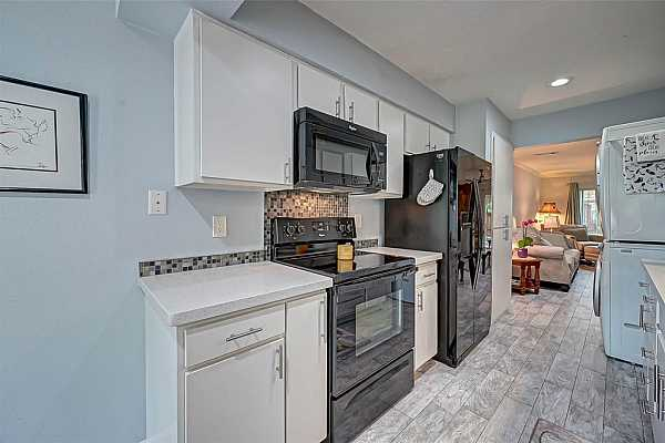 Photo #10 Lovely kitchen with quartz counters, tiled back splash, storage, pantry, broom closet and stacked full size washer & dryer.