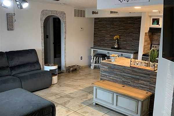 Photo #3 Entry into spacious living area with decorative archway and tile through out