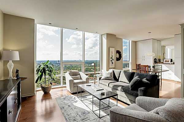 Photo #4 The view of the expansive living & dining areas shows the spaces flowing flawlessly into each other. Natural light streams in from the windows which are equipped with electronic solar shades. The expansive living & dining areas are perfect for entertaining or simply relaxing.