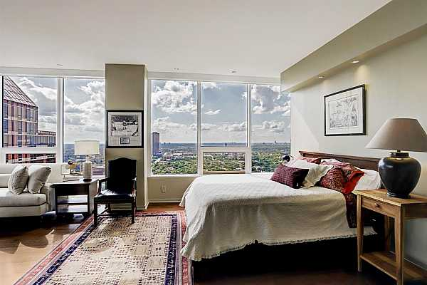 Photo #10 The primary bedroom is a grand retreat with magnificent views & an abundance of natural light. Electronic solar shades, recessed lighting, and beautiful hardwood floors create a serene elegant atmosphere.