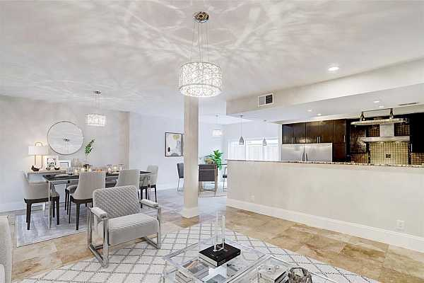 Photo #1 Ideal for entertaining, the living room is graced by an open kitchen and breakfast room and designer lighting throughout.