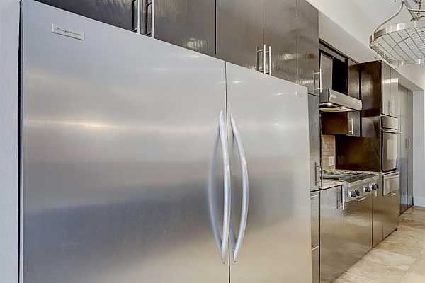 """Photo #10 Note the eye-catching 65"""" Frigidaire stainless steel refrigerator perfect for the aspiring chef."""