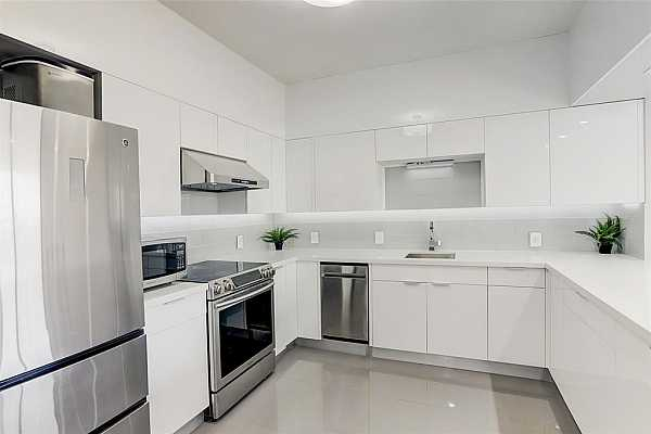 Photo #1 Modern Aesthetic Kitchen with beautiful open concept, glass backsplash, stainless appliances, granite counters, dim lighting & a breakfast bar