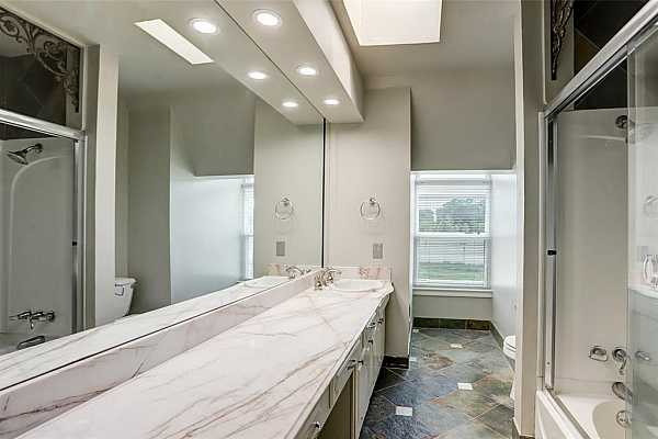 Photo #12 The primary bedrooms ensuite bath offers imported stones and custom features throughout.