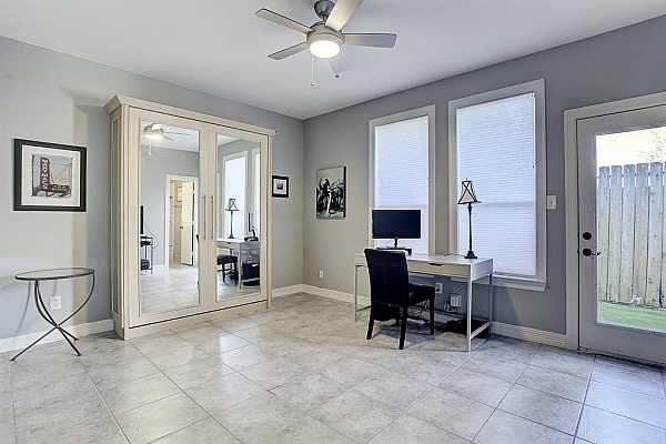 Photo #6 The first floor is a versatile space that can be used as any number of rooms - exercise, secondary bedroom, in-home office, etc.  The mirrored cabinet is actually a Murphy bed, very unique.  The room has an updated full bath, large closet and access to the back patio and yard.
